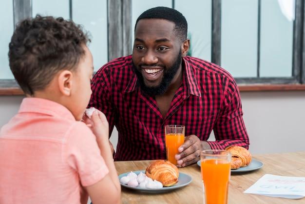 Feliz padre negro e hijo desayunando