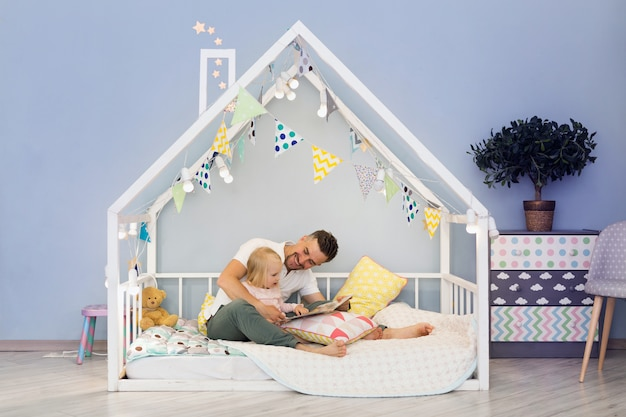 Feliz padre papá en casa linda cama con hija rubia leyendo cuentos antes de acostarse