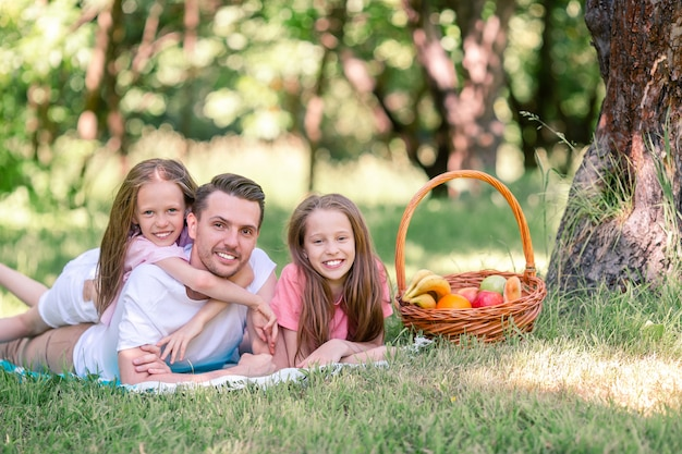 Feliz padre y pequeñas hijas se relajan junto al lago