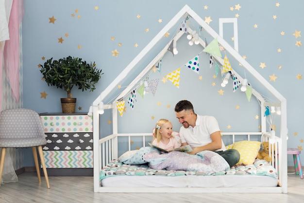 Feliz padre riendo con su niña de 3 años mientras está sentado en la cama de la casa blanca en el dormitorio de los niños