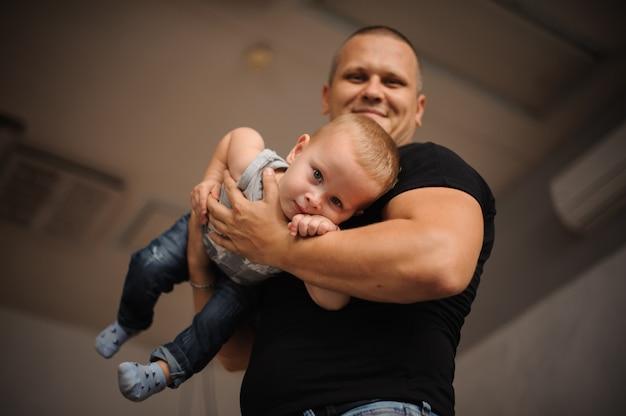 Feliz padre sonriente con un hijo en sus manos