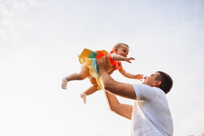 Feliz padre sostiene encantadora niña bajo el cielo de verano