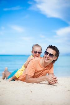 Feliz padre y su pequeña hija adorable tumbado en la playa de arena blanca