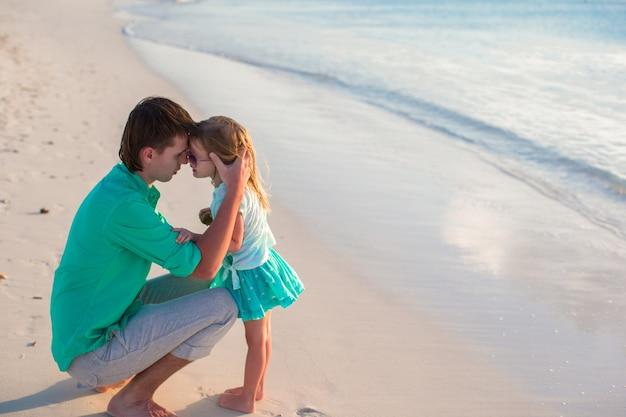 Feliz padre y su pequeña hija linda en la playa
