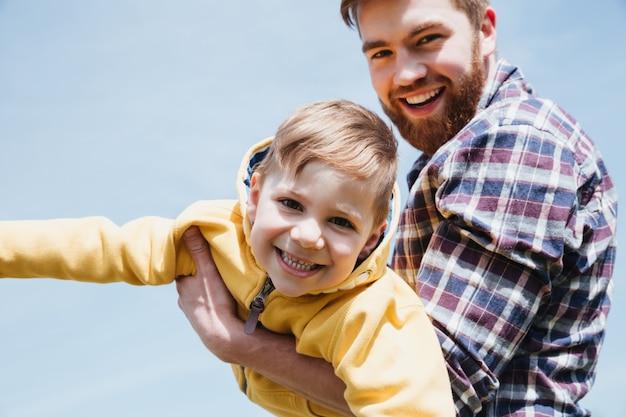Feliz padre y su pequeño hijo divirtiéndose juntos