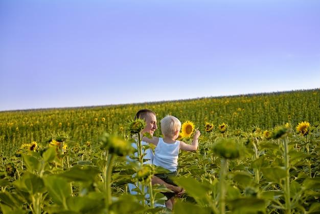 Feliz padre con su pequeño hijo en sus brazos de pie sobre un campo verde de girasoles contra un cielo azul