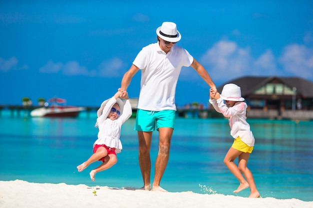 Feliz padre y sus adorables hijas en la playa tropical divirtiéndose