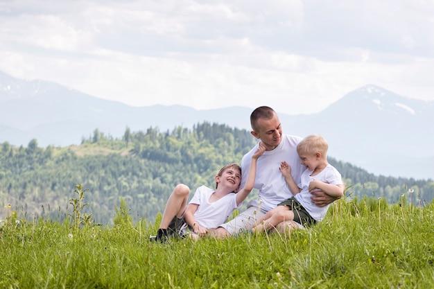 Feliz padre con sus dos hijos pequeños sentados en el césped
