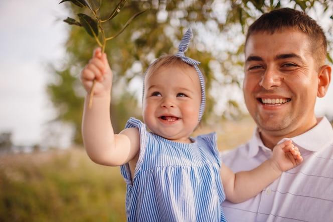 Feliz padre tiene encantadora niña de pie en el jardín