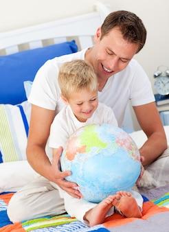 Feliz padre y su hijo mirando un globo terrestre