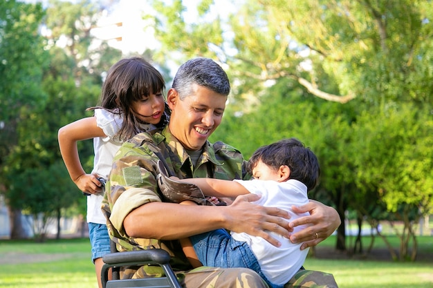 Feliz papá militar discapacitado caminando con dos niños en el parque. niña sosteniendo asas de silla de ruedas, niño descansando sobre el regazo de papá. veterano de guerra o concepto de discapacidad