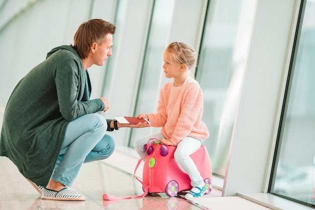 Feliz papá y niña con tarjeta de embarque en el aeropuerto