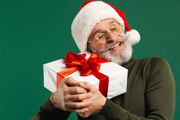 Feliz papá noel moderno barbudo que abraza el regalo