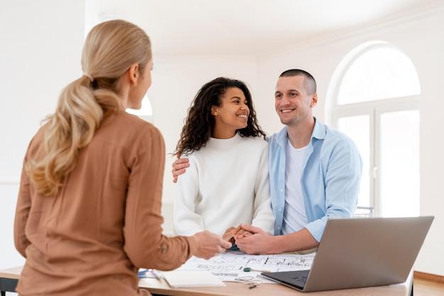 Feliz pareja abrazada conversando con inmobiliaria femenina