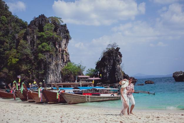 Feliz pareja abrazándose, caminando por la playa contra el mar, montañas, góndolas.