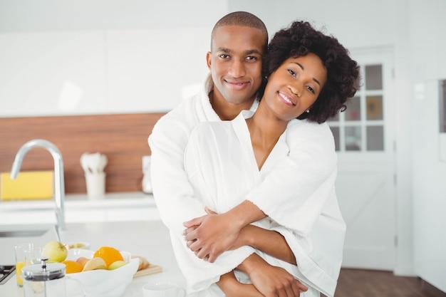 Feliz pareja abrazándose en la cocina en casa