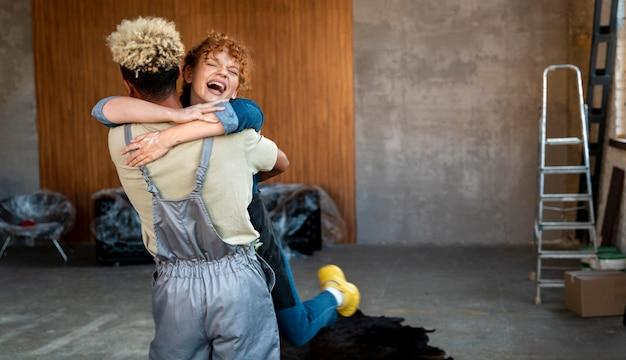 Feliz pareja abrazándose después de mudarse juntos en un nuevo hogar