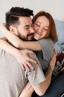 Feliz pareja abrazándose en el interior