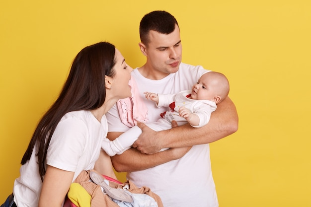 Feliz pareja abrazándose y mirando al niño recién nacido sobre fondo amarillo, hablando con la pequeña hija con amor y sonrisa, padres vistiendo camisetas blancas, familia feliz interior.
