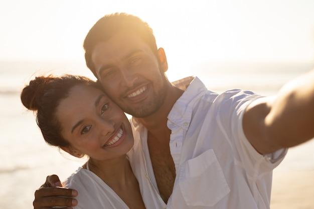 Feliz pareja abrazándose en la playa 4k