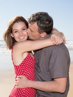 Feliz pareja abrazándose en la playa en un día soleado
