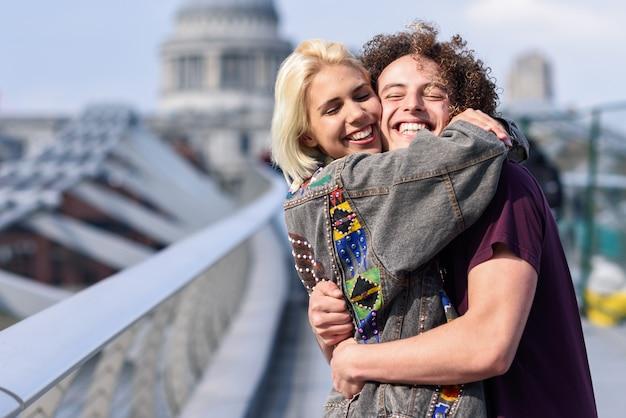 Feliz pareja abrazándose por el puente del milenio, el río támesis, londres.