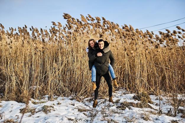 Feliz pareja abrazándose y riendo al aire libre en invierno. foto vapor publicidad ropa de invierno.