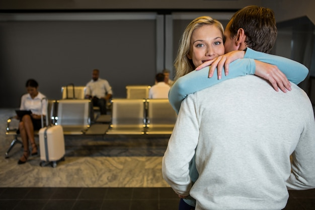Feliz pareja abrazándose en la sala de espera