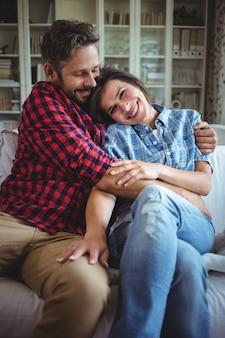 Feliz pareja abrazándose en el sofá en la sala de estar