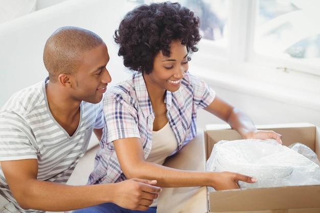 Feliz pareja abriendo cajas en la sala de estar
