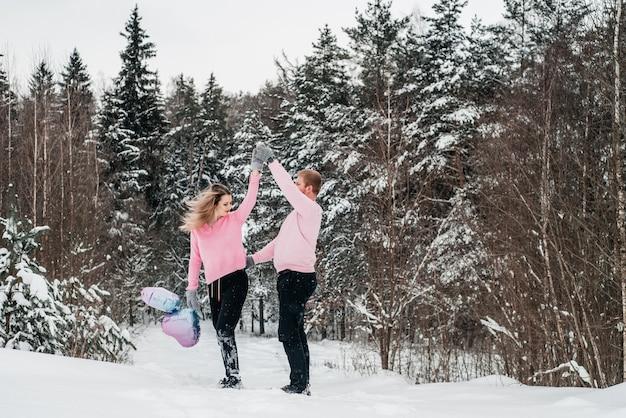 Feliz pareja activa en el bosque de invierno, día de moroz, estilo de vida.