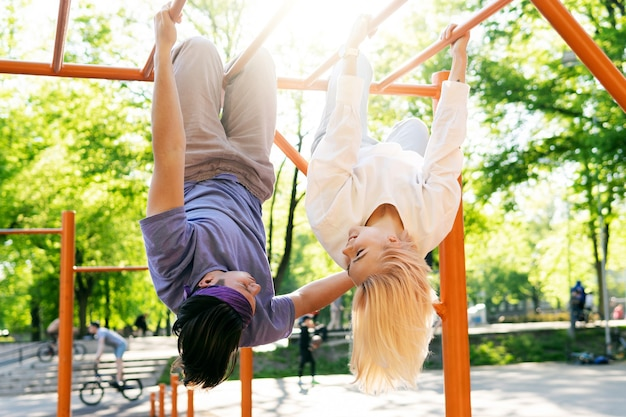 Feliz pareja de adolescentes divirtiéndose en el patio de recreo en un parque de la ciudad
