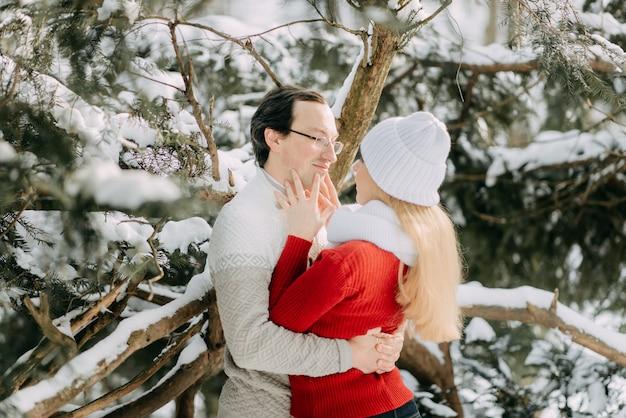 Feliz pareja adulta divirtiéndose en el bosque de invierno y sonriendo, espacio de copia
