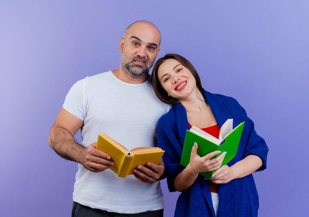 Feliz pareja adulta mujer envuelta en un chal sosteniendo libro y mirando