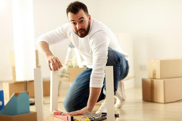 Feliz pareja adulta tratando de montar muebles