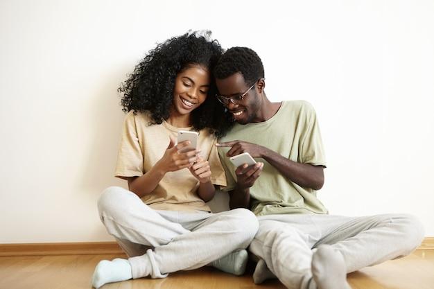 Feliz pareja africana joven vestida casualmente divirtiéndose juntos en casa