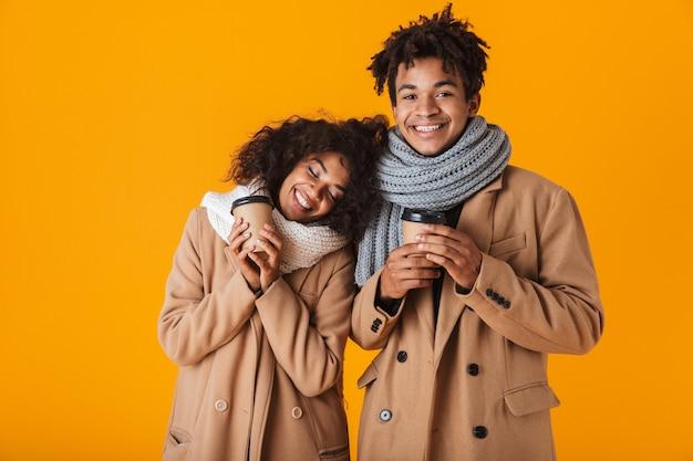 Feliz pareja africana vistiendo ropa de invierno de pie bajo un paraguas aislado, sosteniendo tazas de café para llevar