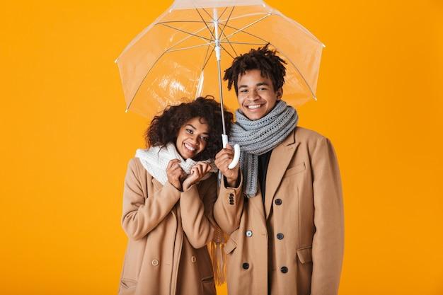Feliz pareja africana vistiendo ropa de invierno de pie bajo un paraguas aislado