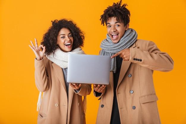 Feliz pareja africana vistiendo ropa de invierno que se encuentran aisladas, sosteniendo la computadora portátil