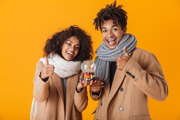 Feliz pareja africana vistiendo ropa de invierno que se encuentran aisladas, sosteniendo el globo de nieve de navidad, pulgares arriba