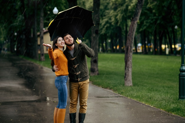 Feliz pareja de amor disfruta de un día lluvioso de verano. el hombre y la mujer están parados bajo el paraguas bajo la lluvia, cita romántica en el sendero, clima húmedo en el callejón