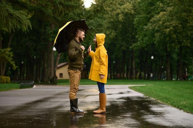 Feliz pareja de amor jura el uno al otro en el parque, día lluvioso de verano. hombre y mujer bajo el paraguas bajo la lluvia, cita romántica en el sendero, clima húmedo en el callejón