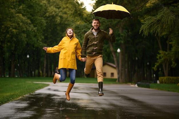 Feliz pareja de amor salta como niños en el parque, día lluvioso de verano. hombre y mujer bajo el paraguas bajo la lluvia, cita romántica en el sendero, clima húmedo en el callejón