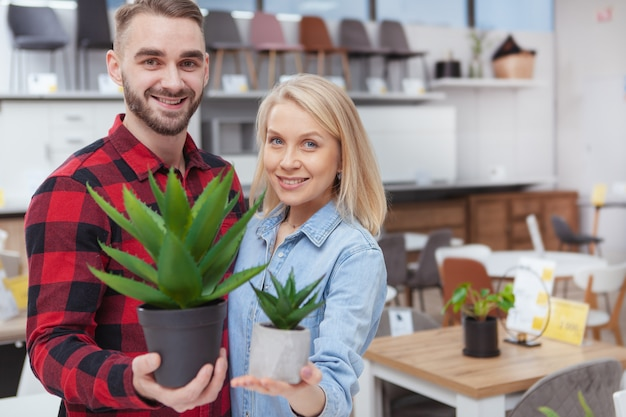 Feliz pareja amorosa abrazando, sonriendo a la cámara con plantas de aloe en maceta