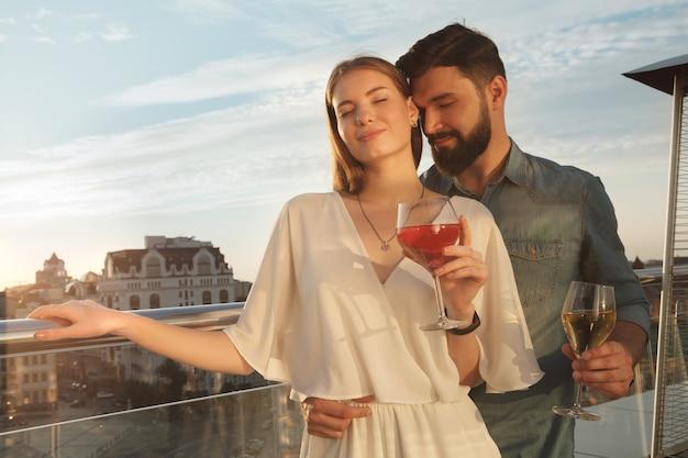 Feliz pareja amorosa abrazándose al atardecer, bebiendo vino en el balcón