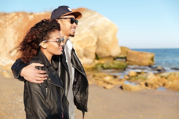 Feliz pareja amorosa africana caminando al aire libre en la playa