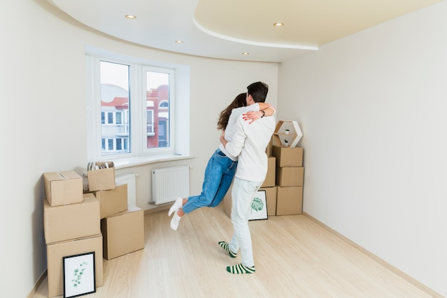 Feliz pareja amorosa con cajas de cartón en casa nueva en el día de mudanza