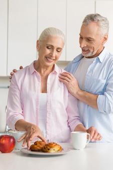Feliz pareja amorosa madura en la cocina cerca de pasteles
