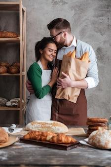 Feliz pareja amorosa panaderos de pie cerca de pan y abrazos