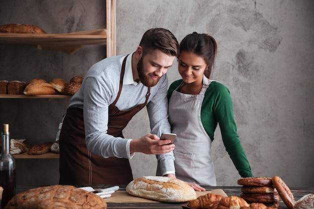 Feliz pareja amorosa panaderos de pie cerca de pan con teléfono